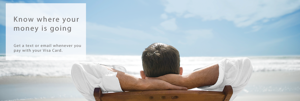 Man sitting carefree on a beach - Let Catlin Bank Visa Alerts make life easy for you.